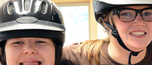 two female campers with horseback riding helmets