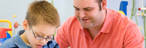 young boy reading with speech therapist