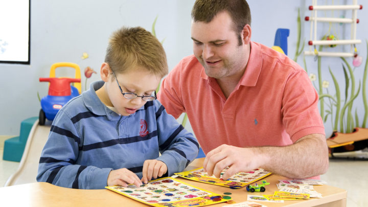 speech pathologist working with young boy