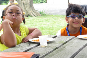 two children at table eating lunch