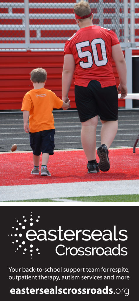 child walking hand-in-hand with football player