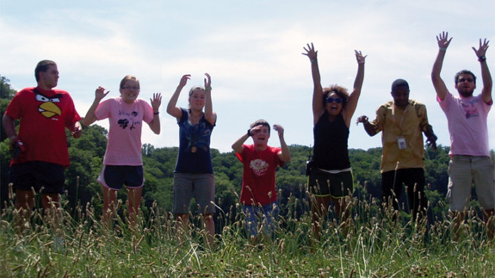 7 campers jumping in field