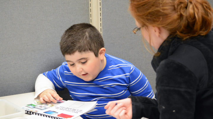 young boy reading with therapist