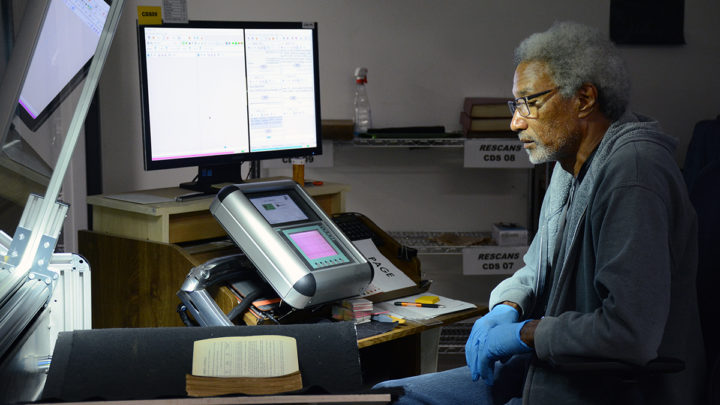 male worker scanning large volume historical book