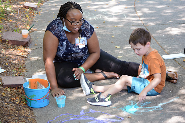 boy and adult painting with sidewalk paint