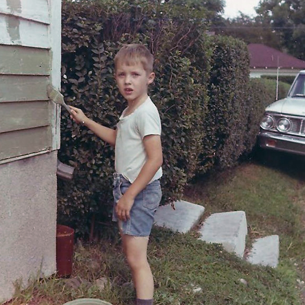 image of Richard painting on the side of a house in the 1960s