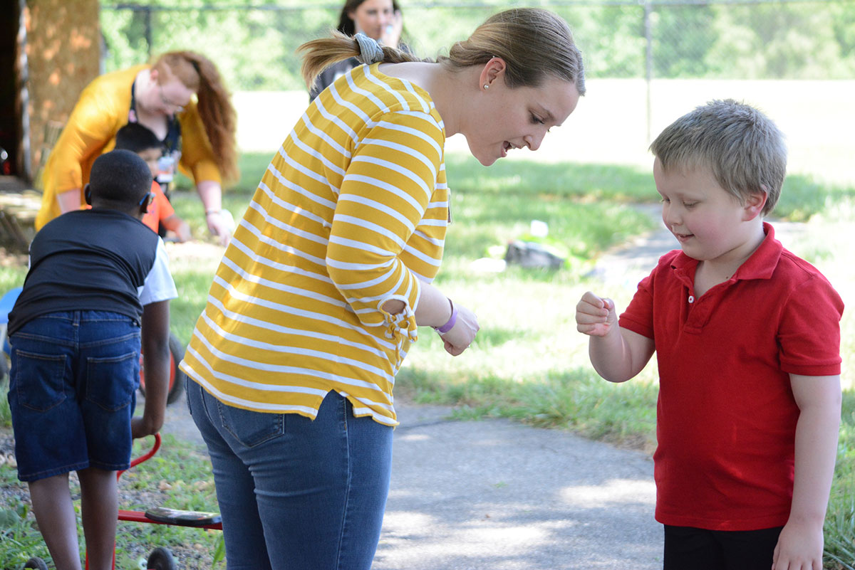 Group of people outside. Boy showing something in his hand to a lady.