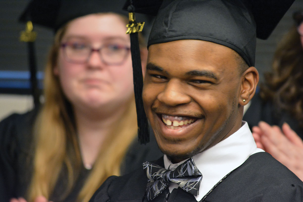 Man smiling in a graduation gown.