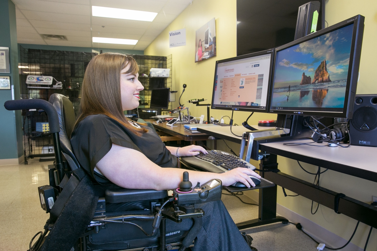 Woman in wheelchair working on computer.