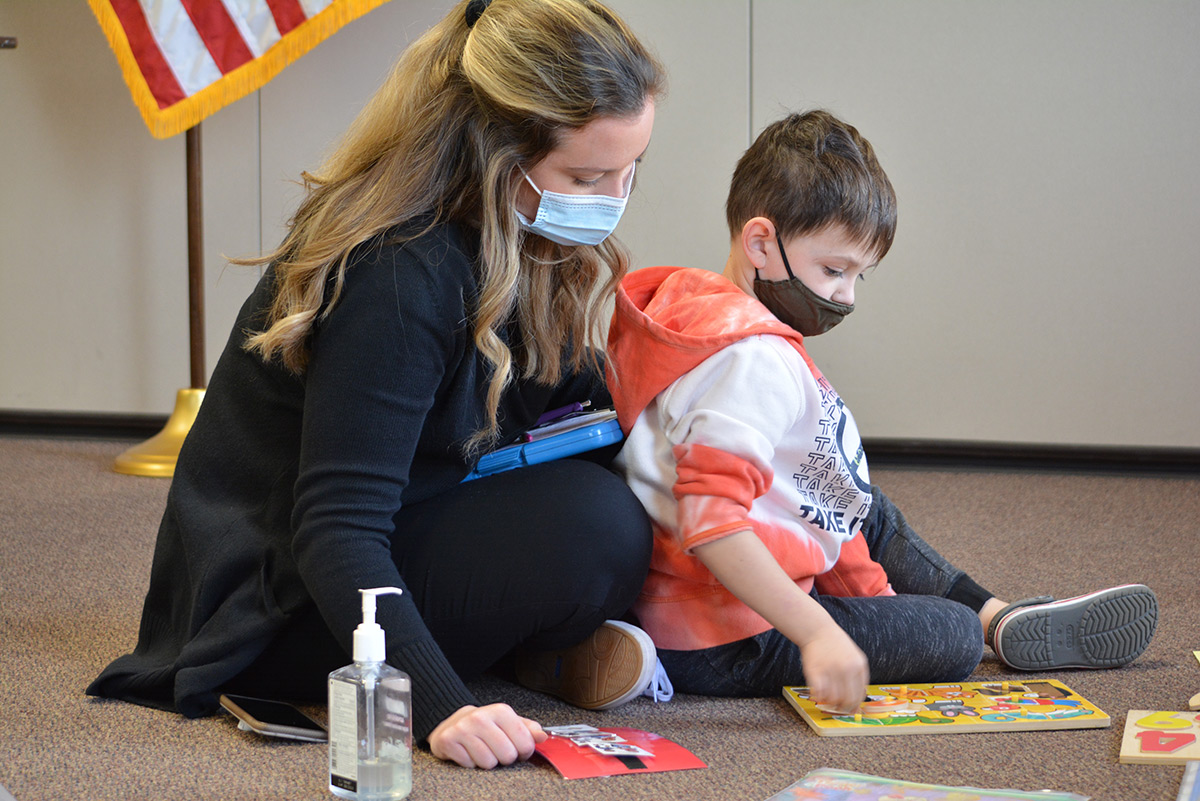 A lady and a boy doing a puzzle with masks on.