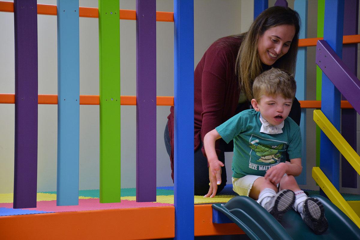 A lady helping a boy down a slide.