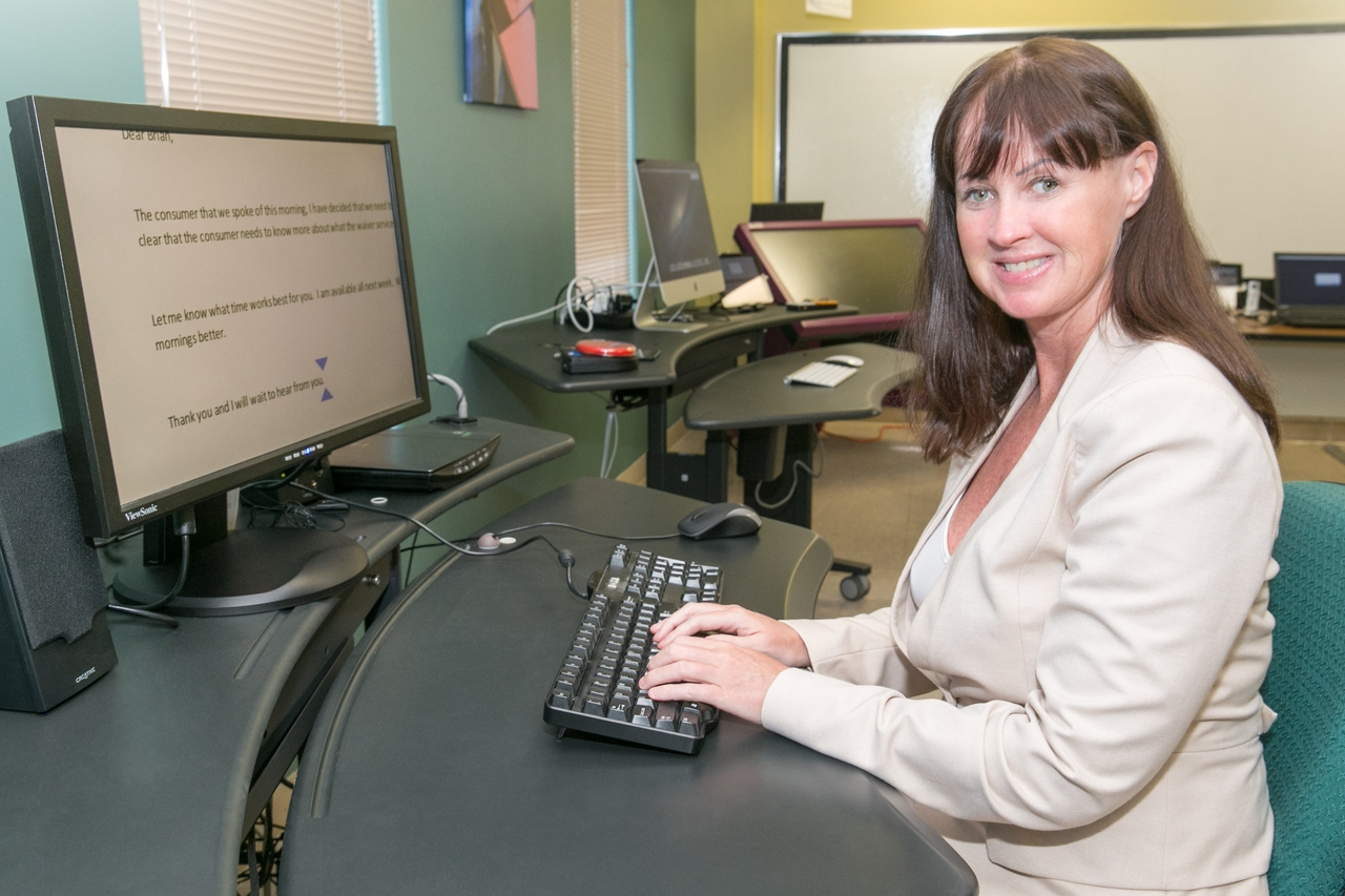 Woman sitting at desk using a computer