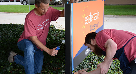 Two volunteers painting an Easterseals Crossroads sign.