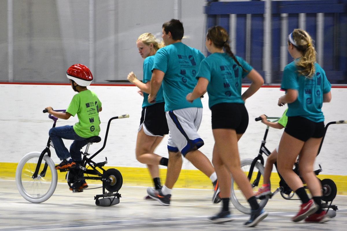 ESC team members running along side of kids riding bikes on ice rink