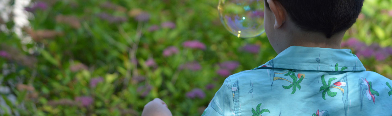 A boy blowing bubbles outside.