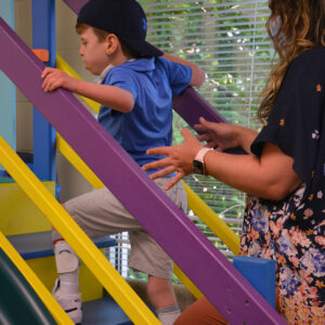 young boy climbing stairs with therapist